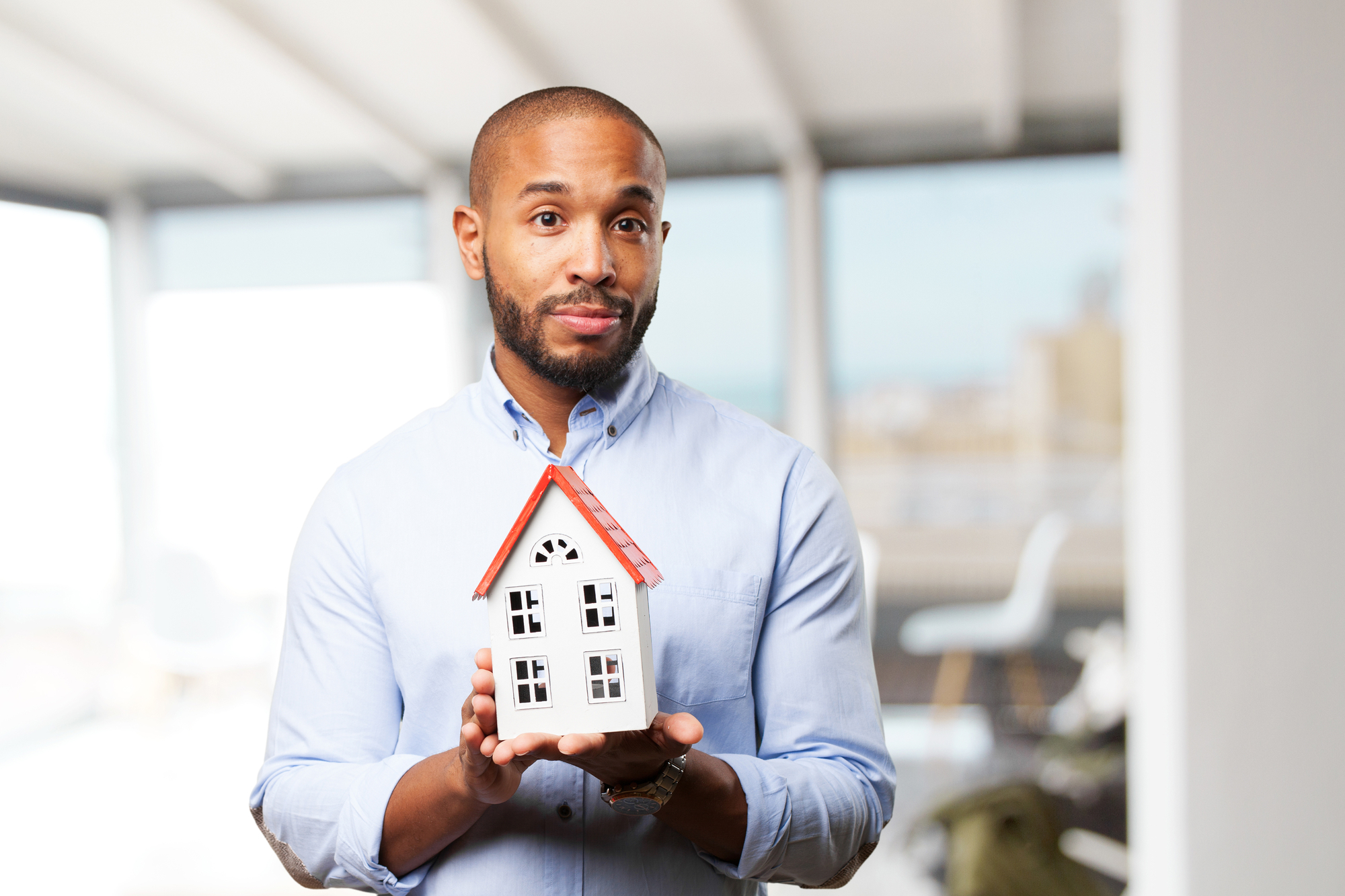 Black businessman with toy house