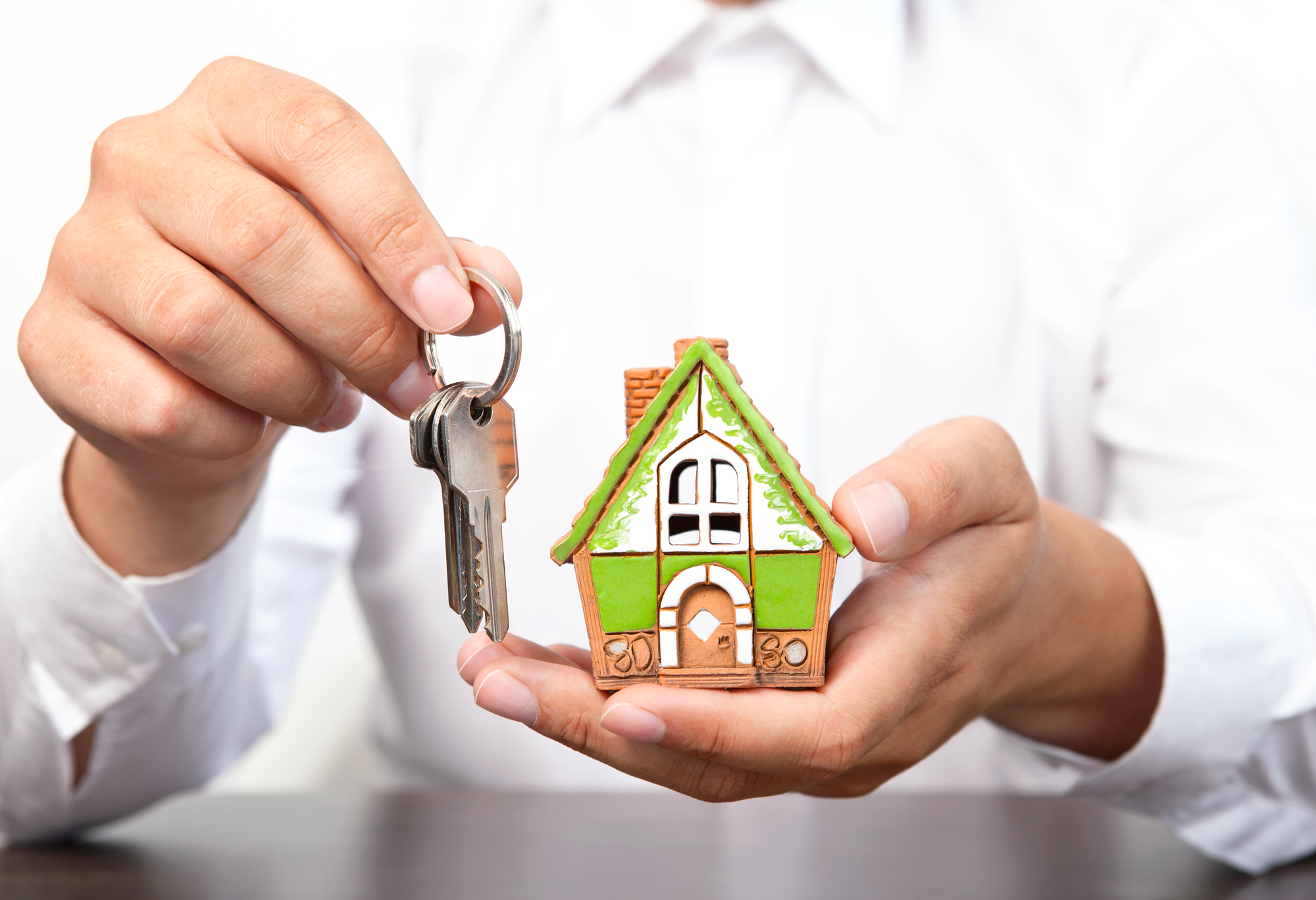 Businessman holding a small house and apartment keys in hand