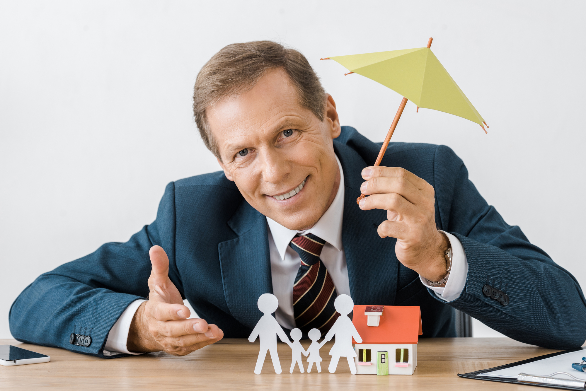 Businessman holding umbrella with paper cut family and house model on wooden table