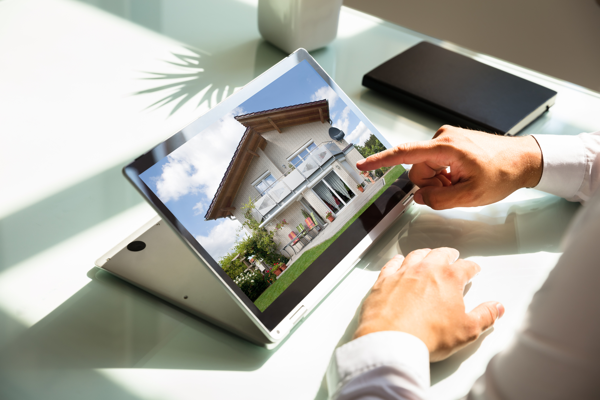 Close-up of businessmans hand checking house on laptop-1