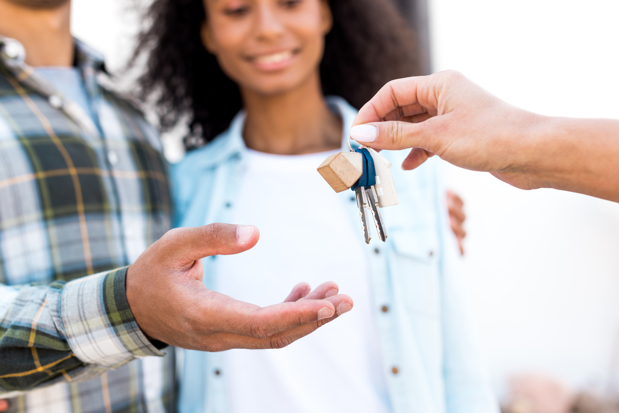 Cropped view of african american woman giving key of new house to happy couple