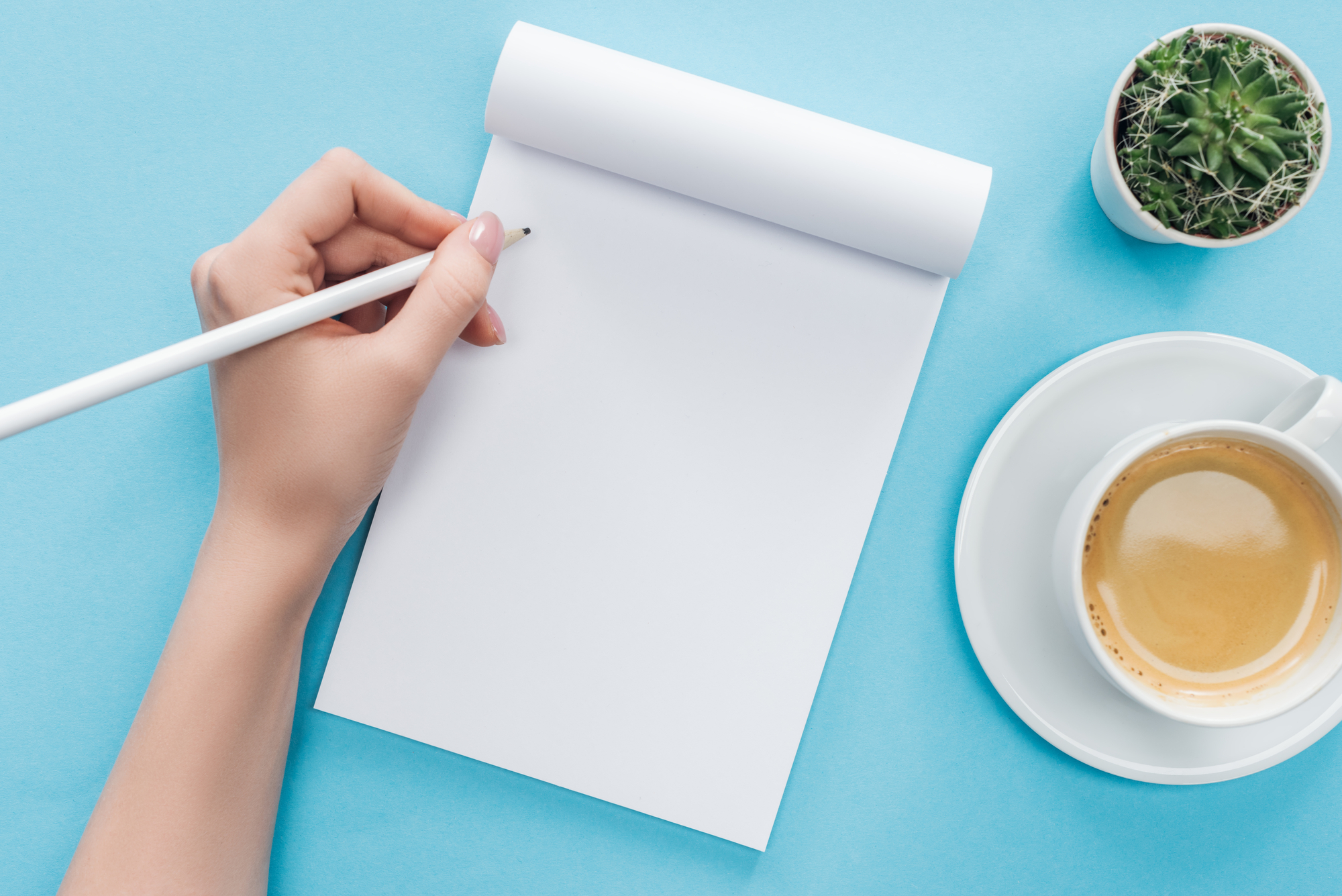 Cropped view of person writing in blank notebook with cup of coffee on blue background