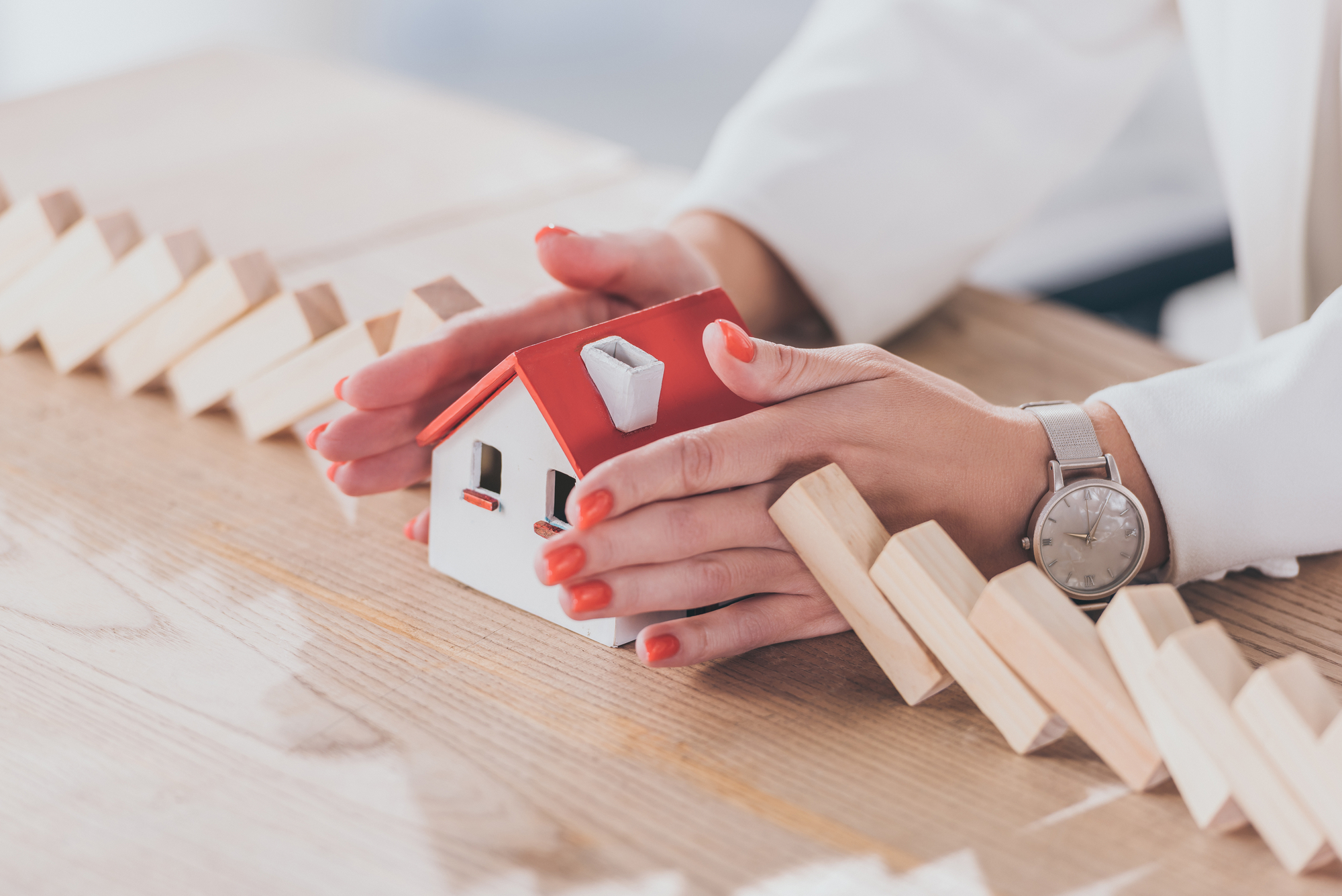 Cropped view of risk manager protecting house model from falling wooden blocks with hands