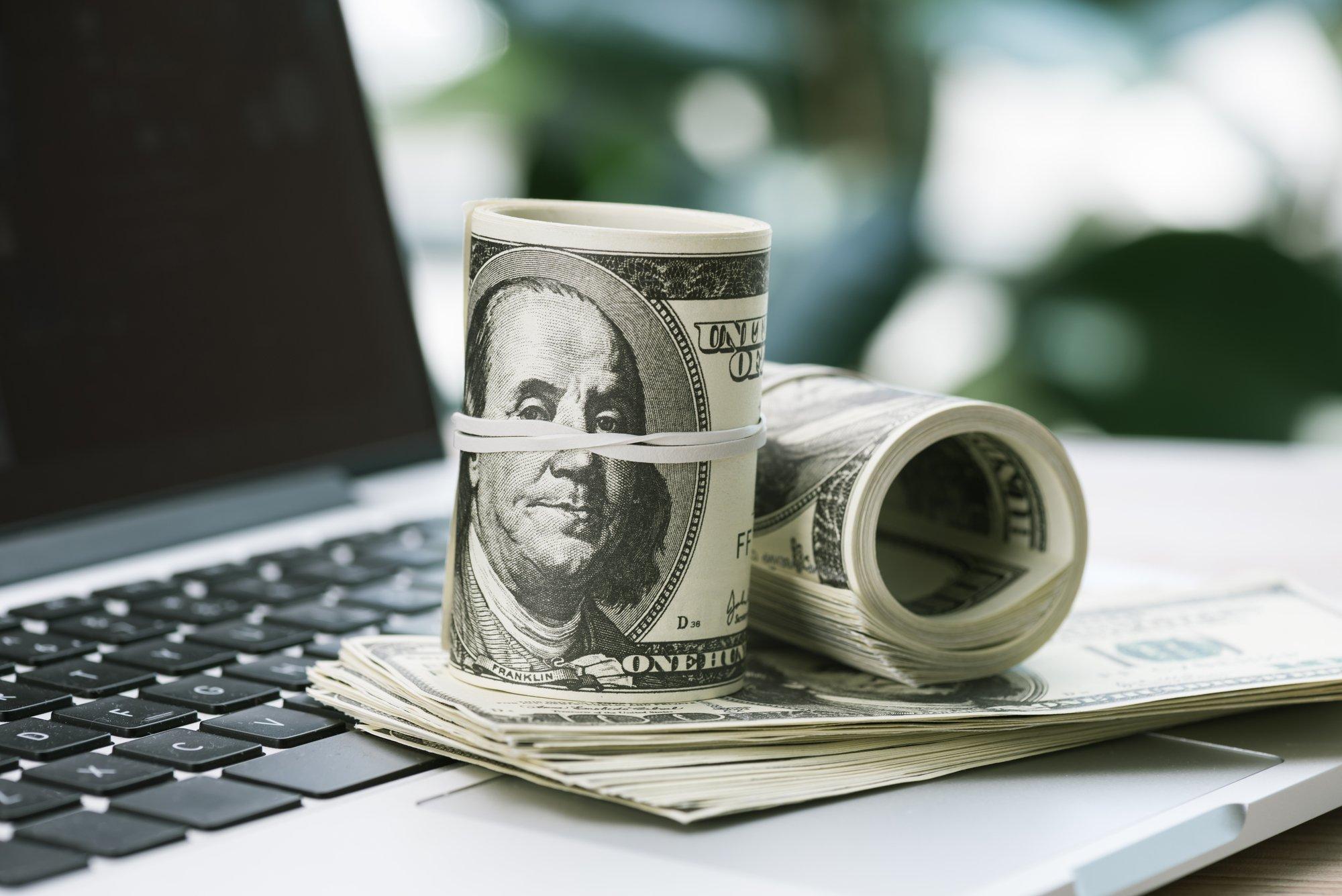 Dollar banknotes on laptop