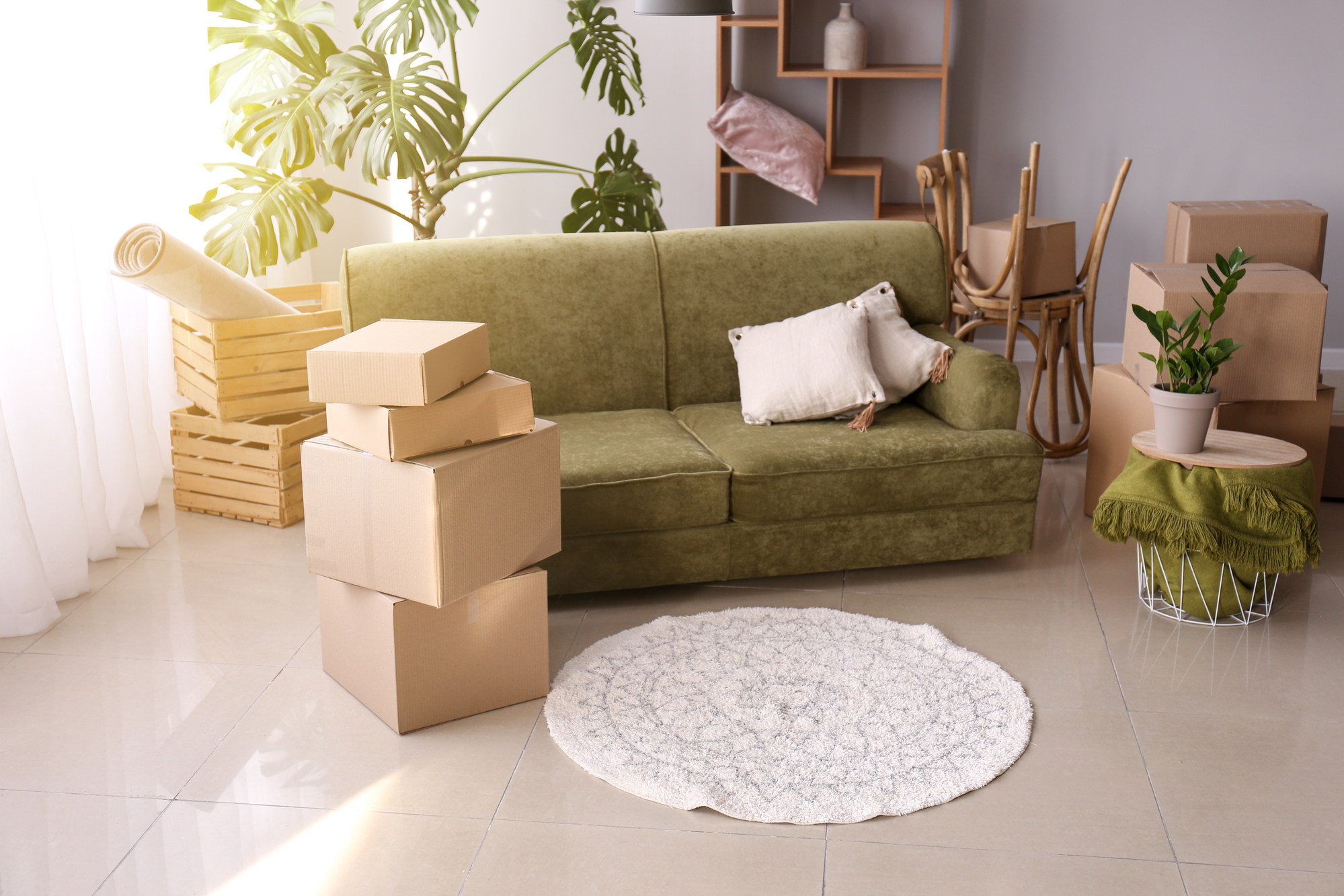 Furniture with moving boxes and belongings in room