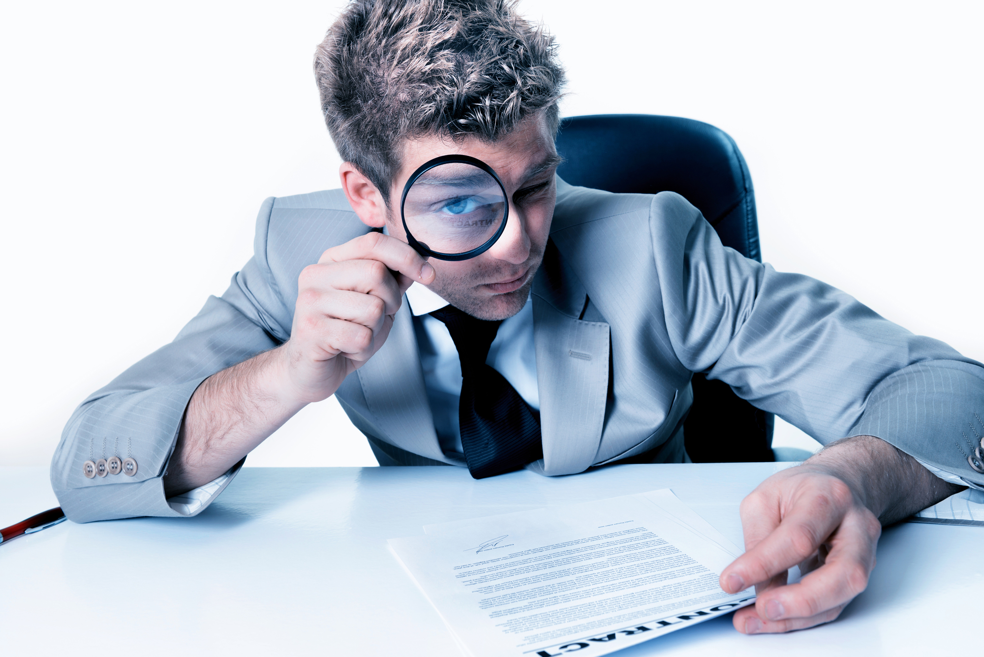 Handsome businessman with magnifying glass study contract