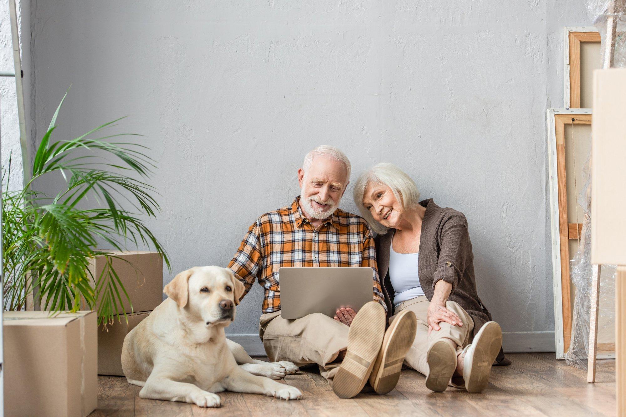 Happy senior couple using laptop sitting on floor and husband petting dog lying near