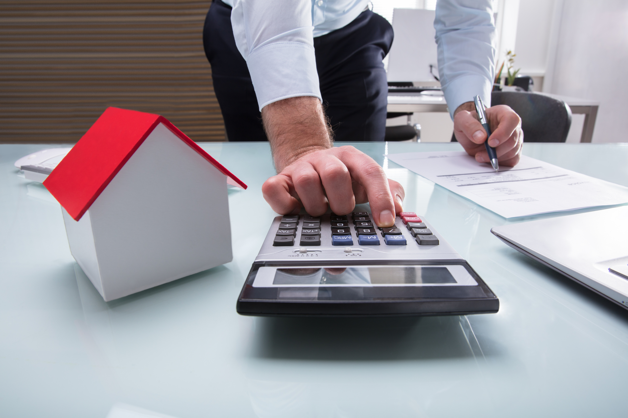 Human Hand Calculating Bill Using Calculator With House Model On Desk