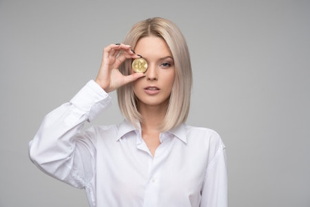 blond-woman-white-shirt-coin-hand-face