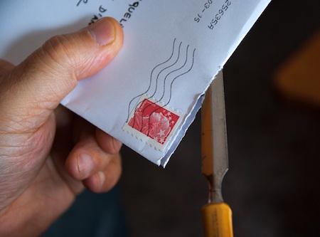 hand-holding-envelope-stamp-opener