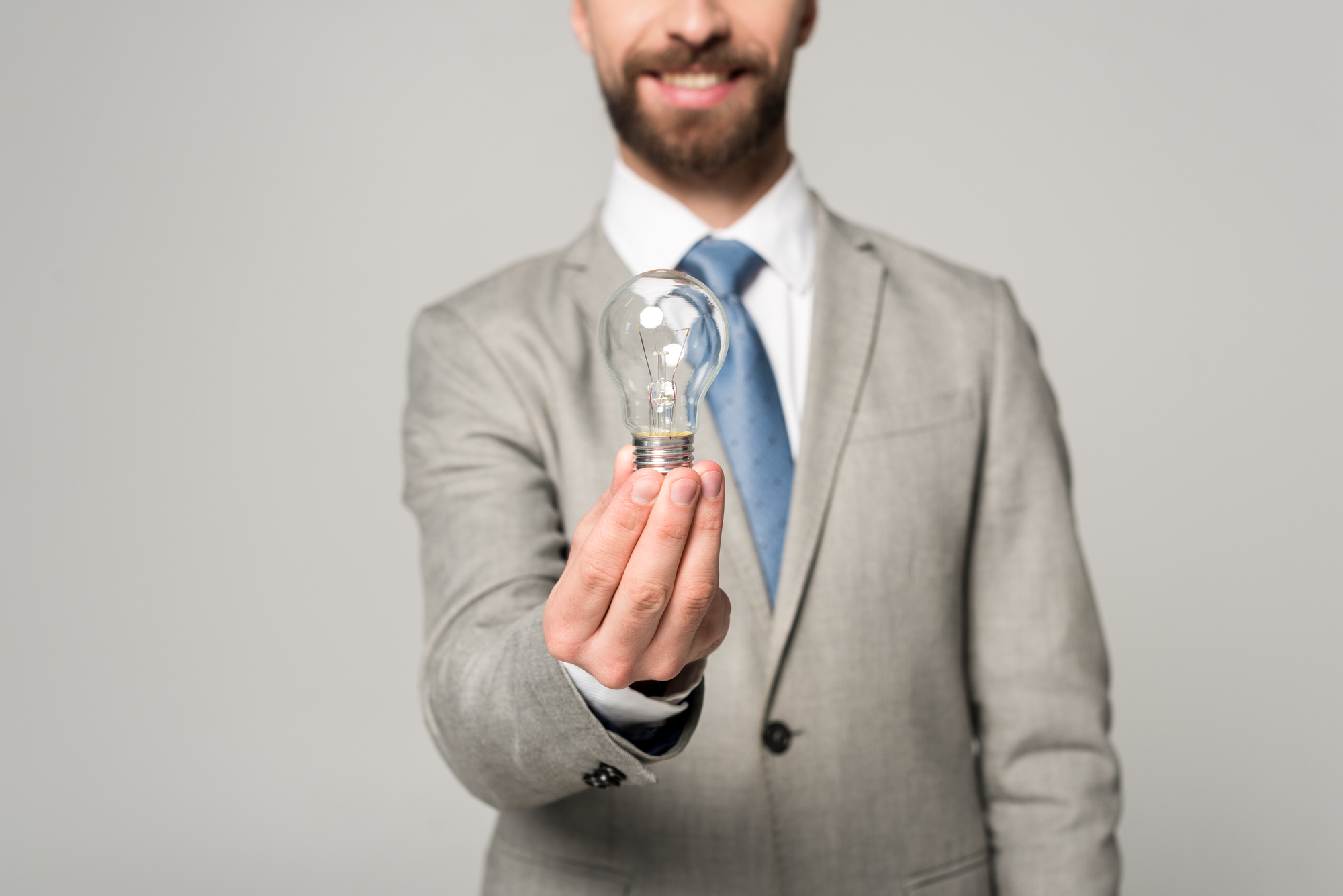 Partial view of smiling businessman holding light bulb isolated on grey