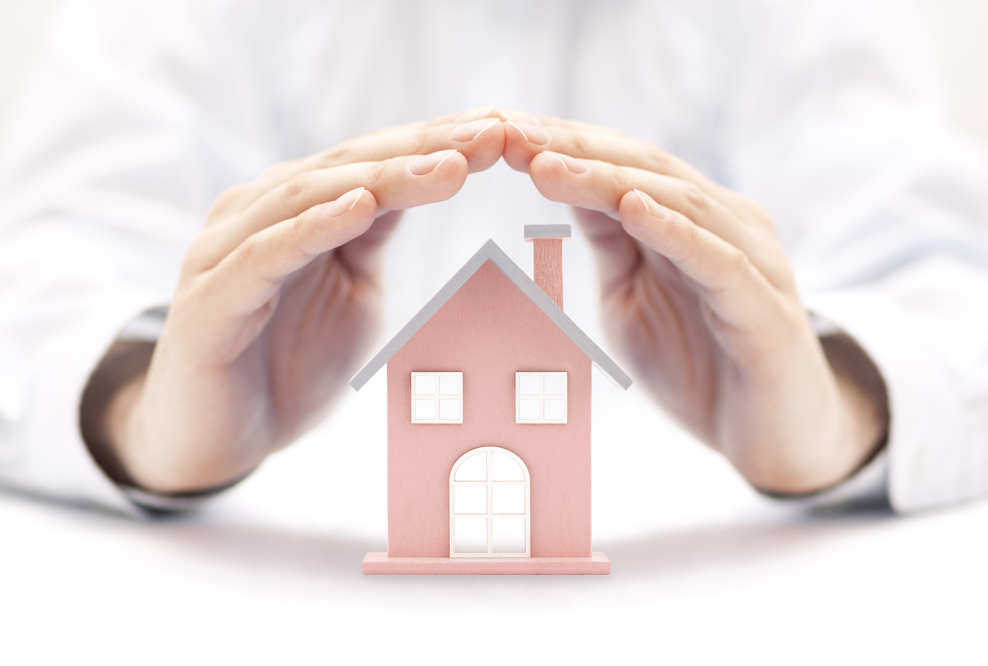 Property insurance. House miniature covered by hands