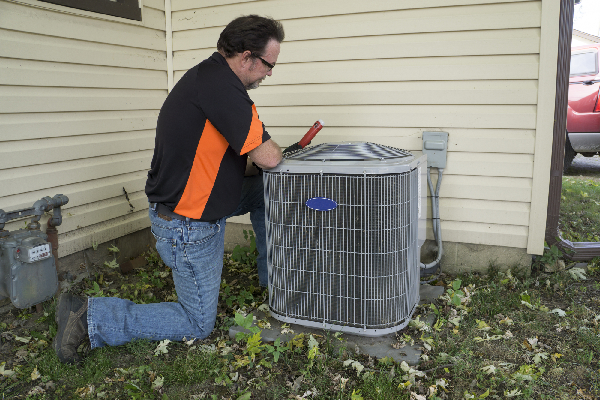 Repairman Checking Outside Air Conditioning Unit For Voltage
