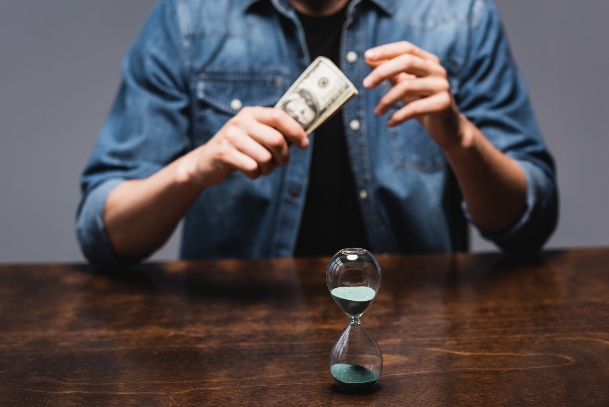 Selective focus of hourglass near man holding dollars while sitting at table isolated on grey, concept of time management