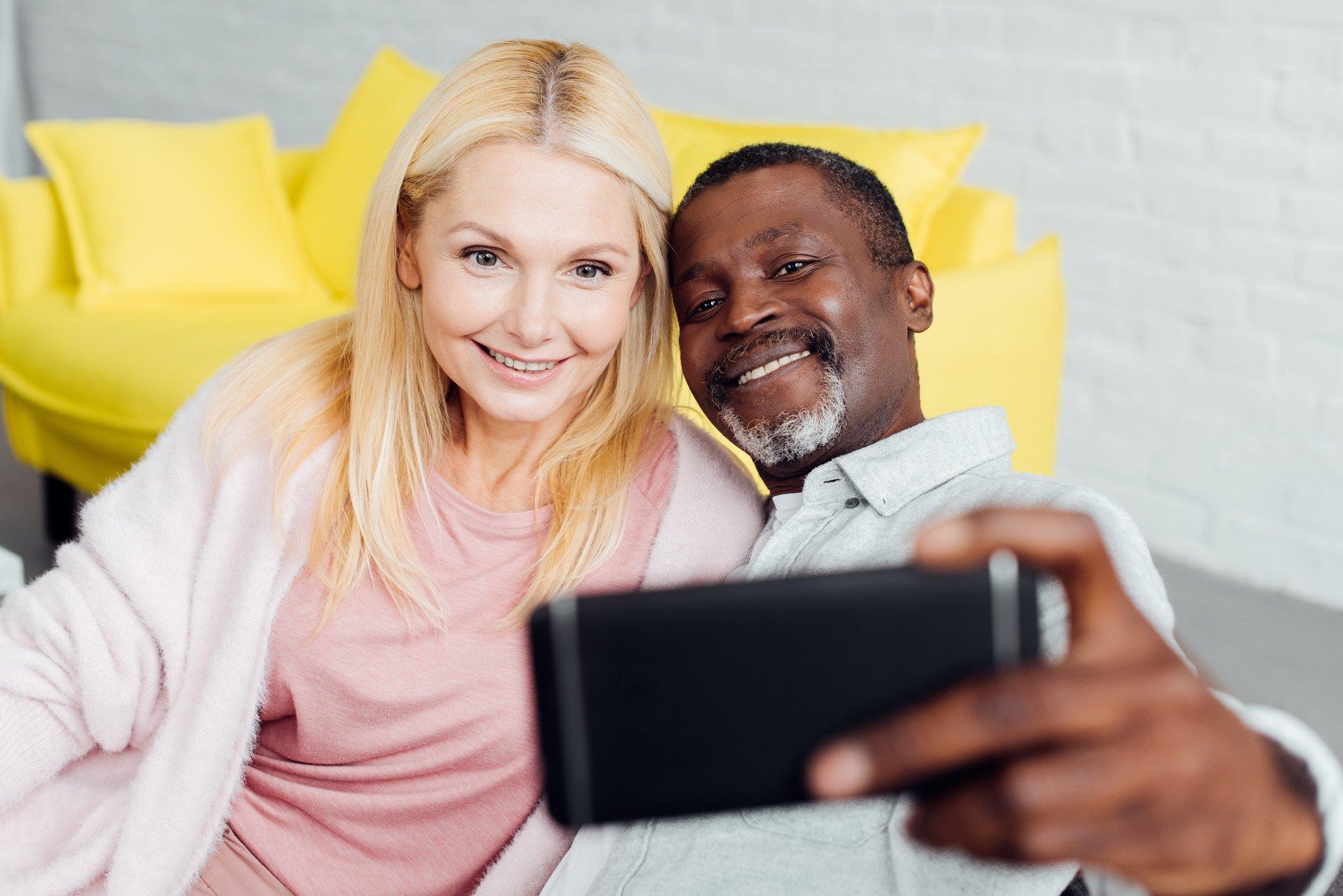 Smiling mature woman and african american man taking selfie