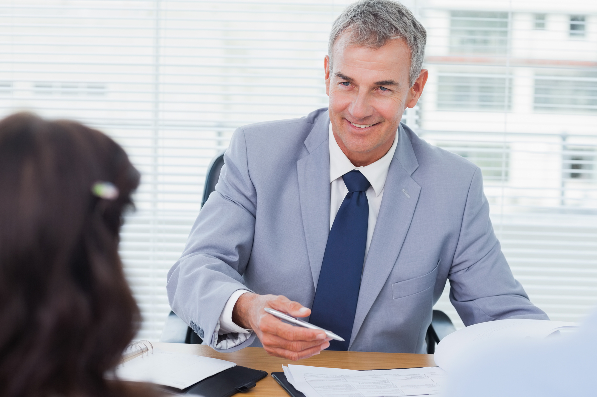 Smiling real estate agent completing contract with couple