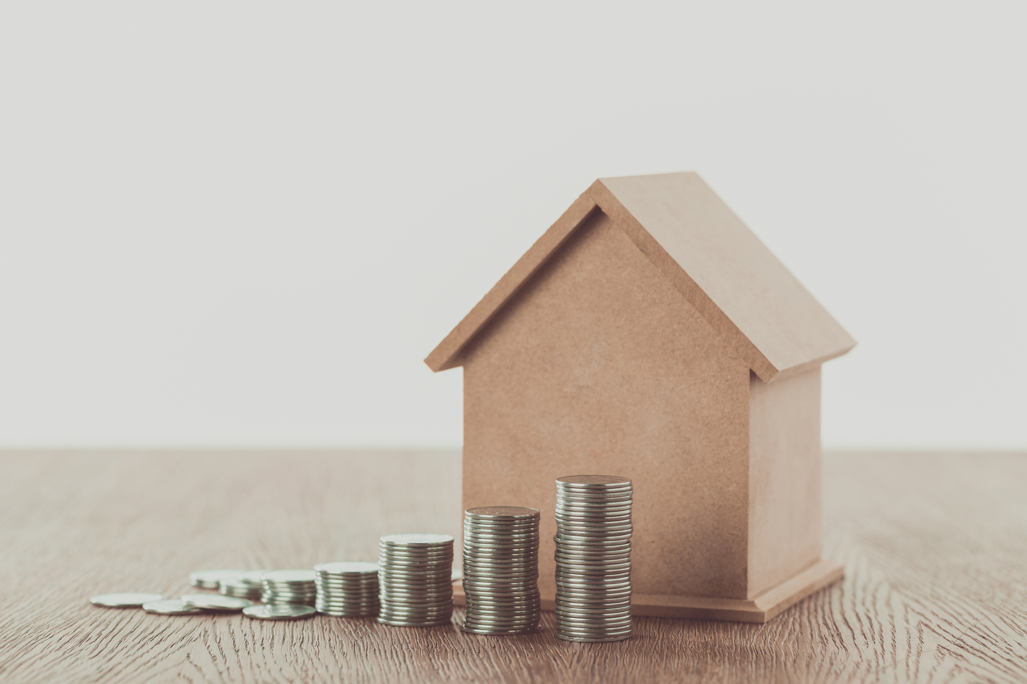 Stacks of coins and small house on wooden table, saving concept