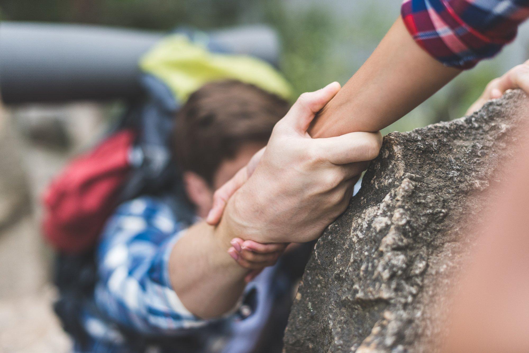 Woman helping boyfriend to climb rock