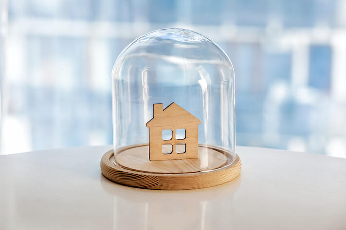 Wooden model of house under glass cap Symbol of safe home. Insurance or protecting building property concept
