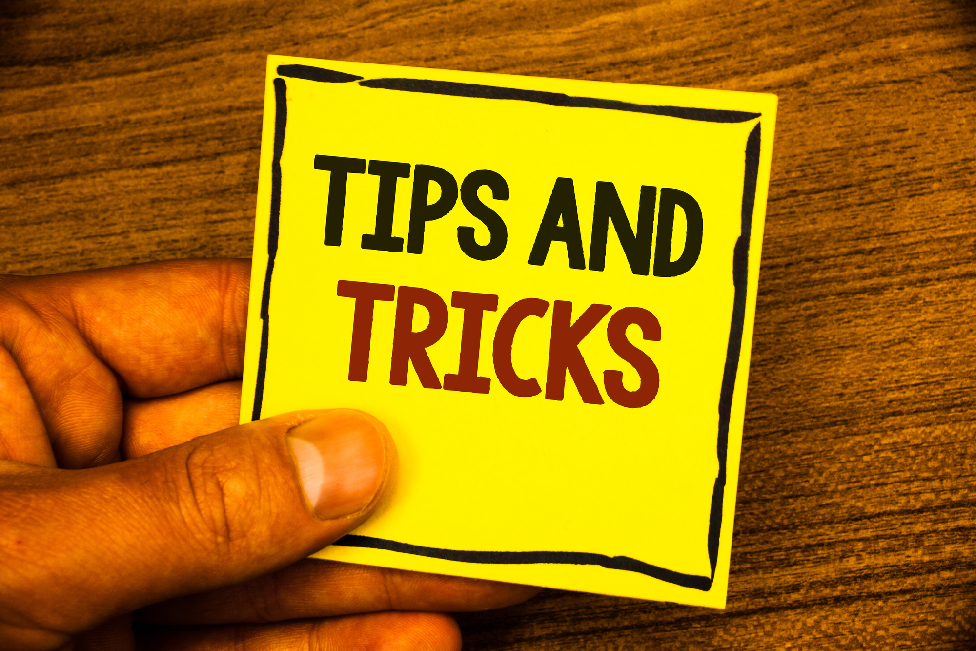 Word writing text Tips And Tricks. Business concept for Suggestions to Make things easier Helpful Advices Solutions Man holding yellow paper ideas black red letters frame wooden background