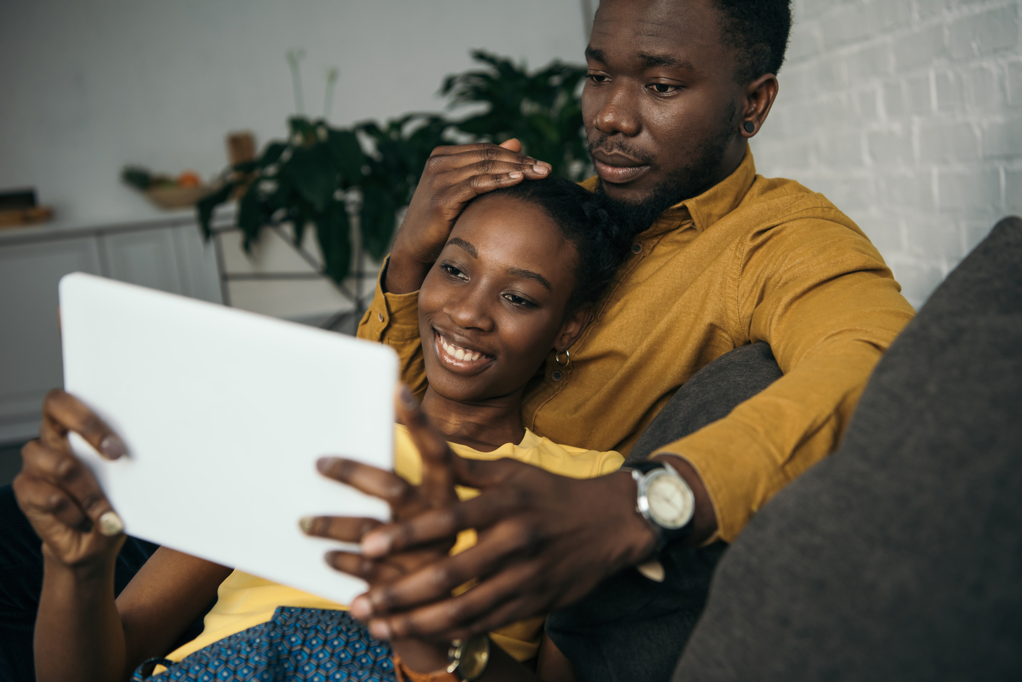 Young african american couple using digital tablet together at home
